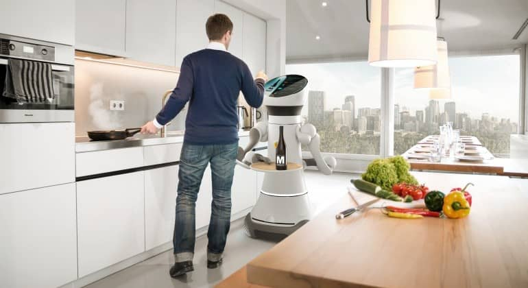 Photo d'un homme cuisinant assité d'un robot